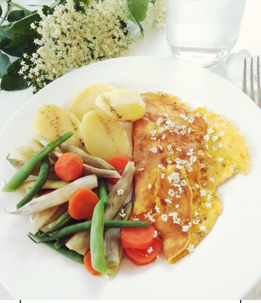 Na tanjuru su kuhani krumpir, mahune i omlet ukrašen cvjetićima bazge,