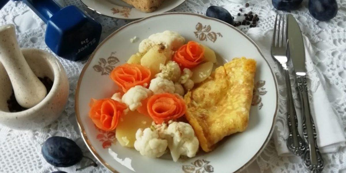 Na tanjuru je lešo kuhana cvjetača , mrkva i krumpir, te omlet. Pokraj su kruh i šljive kao desert.